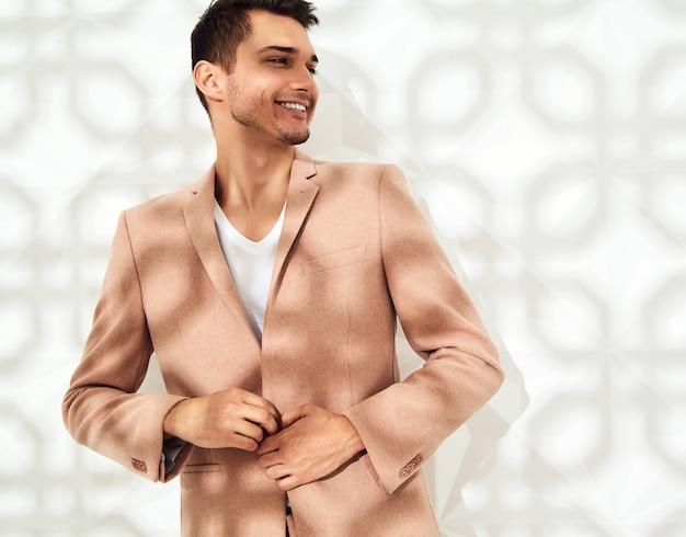 Fashion stylish model dressed in elegant light pink suit posing near white wall