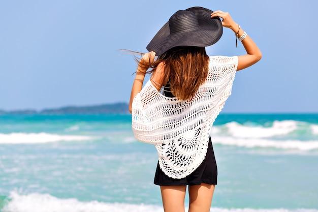 Модный летний образ женщины, позирующей спиной, у синей морской воды, в хороший солнечный летний день, расслабьтесь и наслаждайтесь свободой, радостью, счастьем, яркими цветами