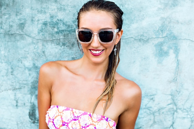 Fashion summer image of sexy young woman wearing bright printed bikini and vintage sunglasses, wet body and hairs, urban wall, vacation style.