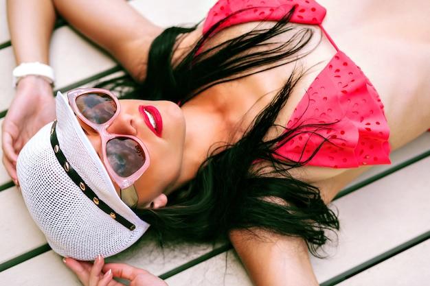 섹시 슬림 그을린 갈색 머리 여자의 패션 여름 야외 초상화, 미니 비키니, 세련된 모자와 선글라스를 착용하고 고급 호텔에서 휴식을 취하고 열대 지방에서 휴가를 보냅니다.