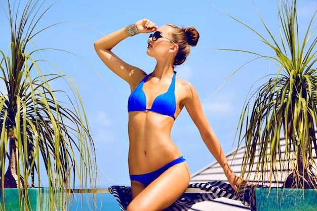 럭셔리 휴가에 편안한 완벽한 슬림 맞는 몸매를 가진 젊은 섹시한 멋진 여자의 패션 여름 초상화. 세련된 밝은 비키니 메이크업과 선글라스를 착용하십시오.
