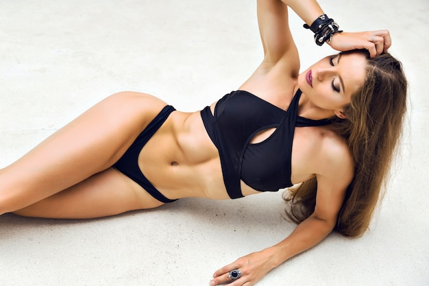 Fashion summer portrait of stunning woman with slim sportive fit tanned body