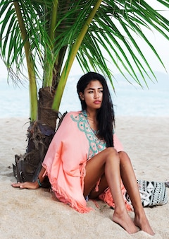 Fashion summer portrait of young beautiful asian model relaxing on tropical beach, wearing boho trendy dress, sitting on white sand near palm tree.