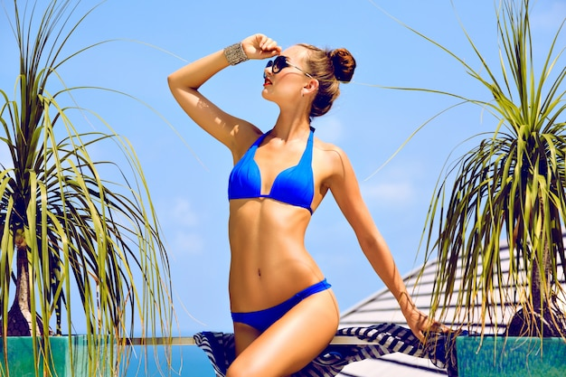 Fashion summer portrait of young sexy stunning woman with perfect slim fit body, relaxed on luxury vacation. wearing stylish bright bikini makeup and sunglasses.