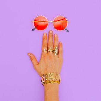 ファッションサングラスとスタイリッシュなゴールドジュエリー。トレンドレディアクセサリー