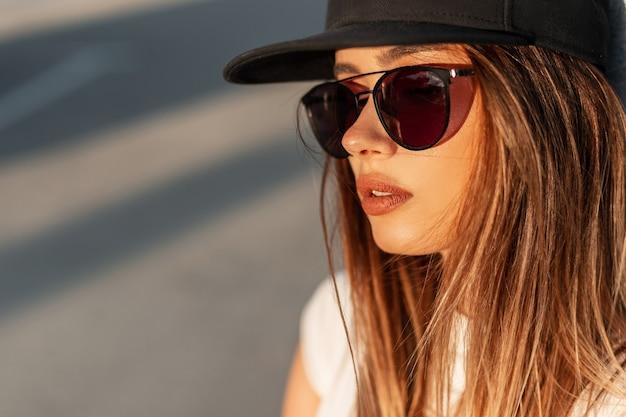 スタイリッシュな黒の野球帽と素晴らしいオレンジ色の夕日の路上で流行のサングラスで柔らかい肌にかわいい唇を持つファッション盗品の若い女の子。太陽の下でクールな現代の女性。クローズアップの肖像画。
