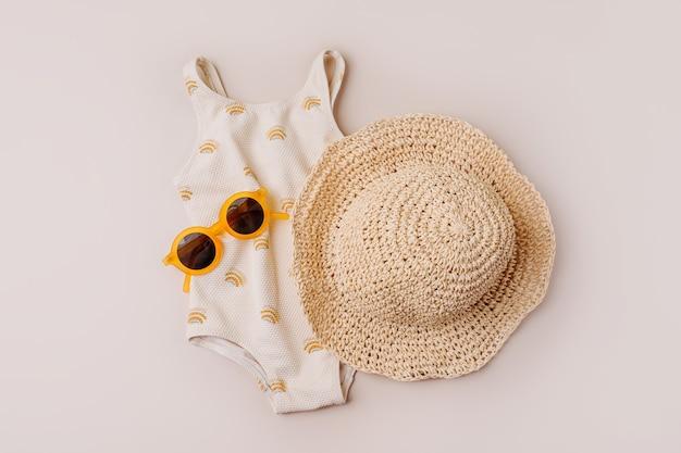 子供のためのファッション水着と帽子。子供のためのビーチサマーアクセサリーの上面図。フラットレイ