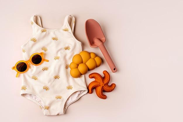 ビーチおもちゃとファッション水着とサングラス。子供のためのビーチサマーアクセサリーの上面図。休暇のためのモダンなセット。フラットレイ