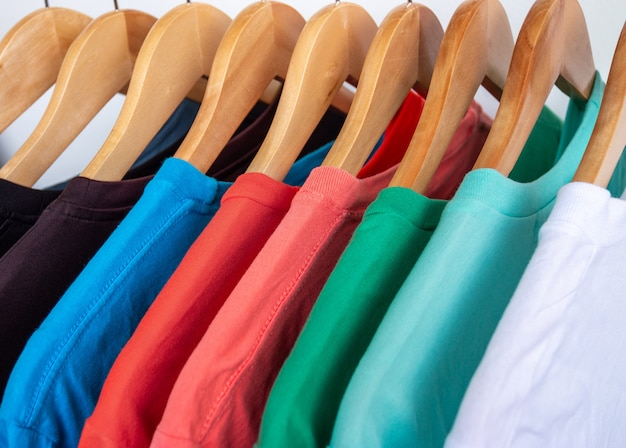 Fashion t-shirt on clothing rack - closeup of bright colorful closet on wooden hangers in store closet.