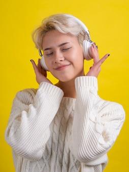 目を閉じて音楽を聴く白い髪のファッションの十代の少女