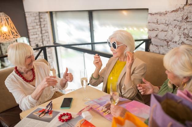 ファッション。新しいサングラスを試しながら楽しい時間を過ごしている3人の女性