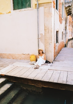 Fashion traveler blogger signs postcard or letter to friend from venice young woman travel italy