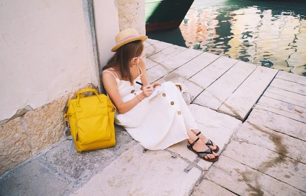 Блогер-путешественник моды подписывает открытку или письмо другу из венеции молодая женщина путешествует по италии