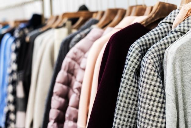 ファッショントレンドのコンセプト。木製ハンガーにニットウールジャンパーをあしらった暖かい冬の婦人服コレクション。