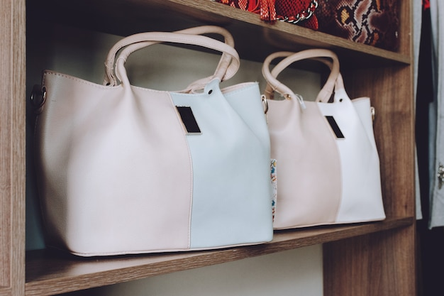 Fashion trend light handbags on shelf in a store, shop.