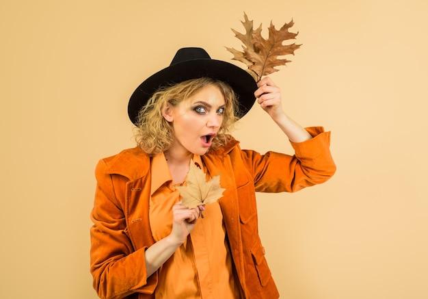 Fashion trends for fall beautiful surprised girl with autumn leaf autumnal foliage autumn sale leaf