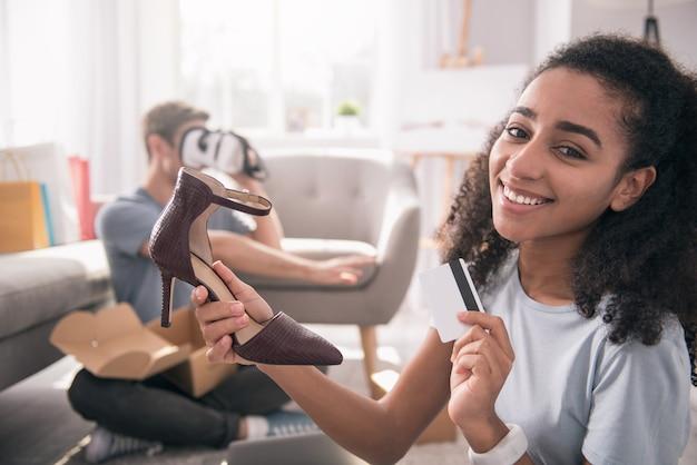 ファッショントレンド。新しい靴を購入しながらクレジットカードを保持している幸せな楽しい女性