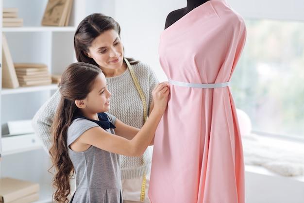 Модные тенденции. позитивная милая довольная девушка смотрит на свое платье и пытается исправить его, изучая дизайн одежды