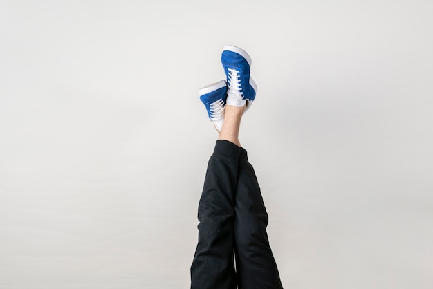 The fashion trendy concept, simple legs in sneakers in air against the wall, upside down