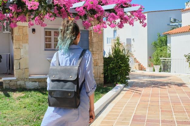 리조트 빌리지에서 화창한 여름 날에 배낭을 걷고있는 파란 머리를 가진 유행 소녀 패션, 갈색 타일 도로 포장, 다시보기 복사 공간을 따라 걸어