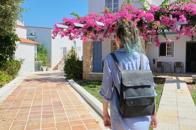 Модная модная девушка с синими волосами с рюкзаком гуляет в солнечный летний день
