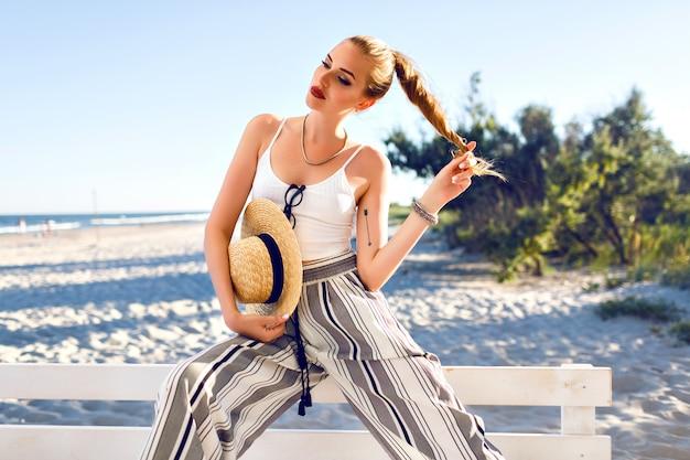Модный летний портрет стильной женщины наслаждается отпуском, полосатыми брюками и соломенной шляпой.