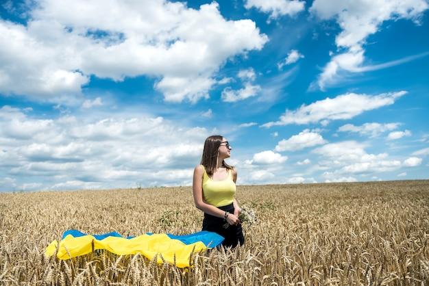 夏の小麦畑に国旗を持つファッションウクライナの女の子