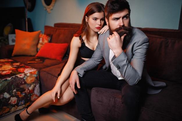 Несчастная пара моды, сидя на диване