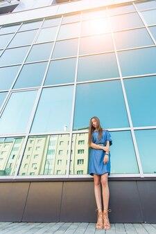 거리에서 아름다운 모델의 패션 도시 초상화. 블루 드레스를 입고 젊은 슬림 여성