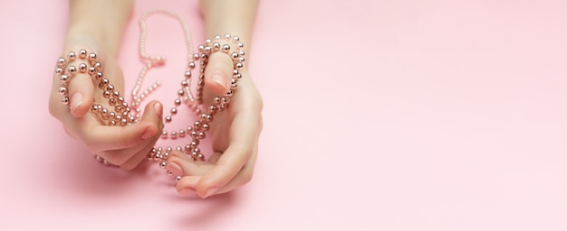 Fashion victim concept flat lay on a pink background. shopaholics woman's hands tied with a rope with beads. compulsive buying disorder.