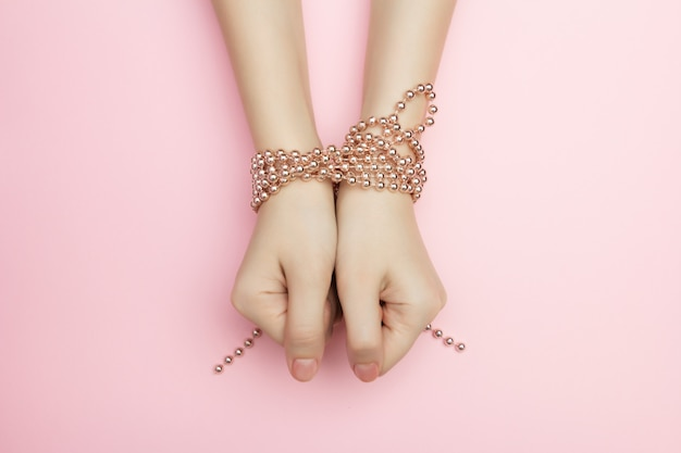 Fashion victim concept flat lay on a pink surface. shopaholics woman hands tied with a rope with beads. compulsive buying disorder.