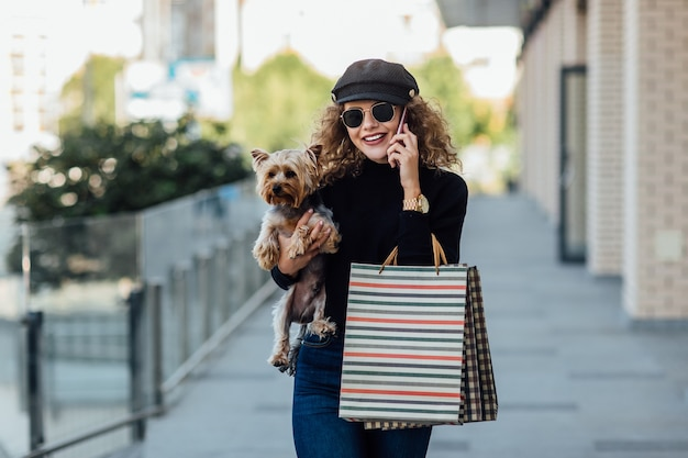 Fashion walk woman with long curly hair holds small dog and shopping bags beautiful girl hugs little dog smiling attractive woman with yorkshire terrier girl with dog in hands and sale concept