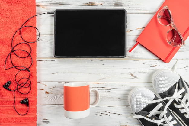 Fashion weekly planner, mug, towel, snickers, modern headphones and tablet on white rustic wood table