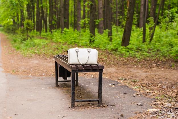 屋外のベンチに白いファッションバッグ