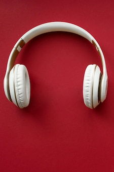 Fashion white headphones on red background. headphones for music sound.