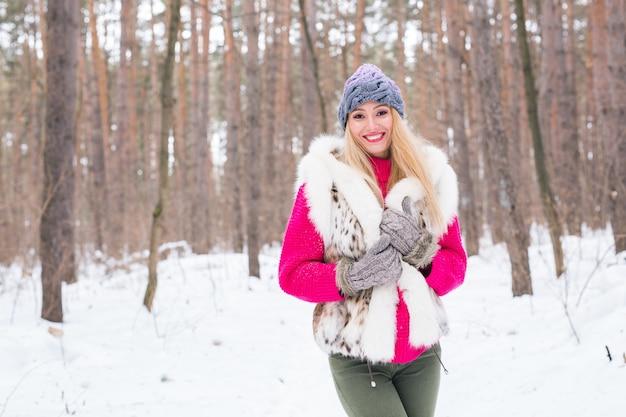 ファッション、冬、人々のコンセプト-雪の上に毛皮のチョッキを着た若い魅力的な女性