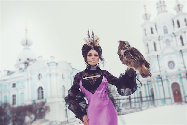 Fashion winter portrait of a beautiful brunette in a long lilac dress with an eagle owl. creative hairstyle and make up