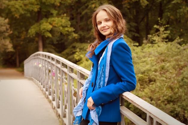 Fashion woman on bridge in autumn park