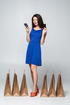 Adatti la donna che compra il cellulare della tenuta e la carta di credito online con i sacchetti della spesa variopinti isolati