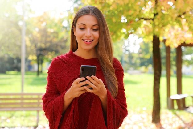 Мода женщины в чате онлайн с умным телефоном в городском парке.