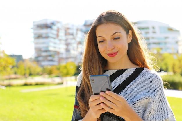 Мода женщина разговаривает с приложением смарт-телефона в городском парке.