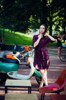Fashion woman in checkered dress posing and pulling her hair near scooter over summer park