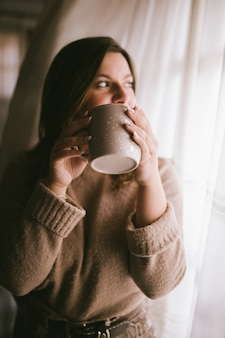 Fashion woman enjoying coffee or tea moment. coffee cup in girl hands. female with cup of hot beverage. winter cup of drink. relaxing concept.