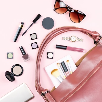 Fashion woman feminine flat lay with beauty products and accessories on pink table