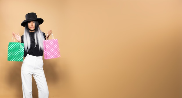 패션 여자 보류 쇼핑 회색 가방, 검은 모자 흰색 바지와 유행 헤어 스타일 아시아 소녀는 분홍색 녹색 가방을 던져