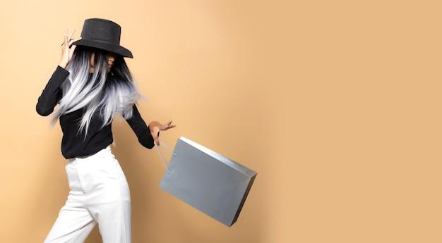 Модная женщина держит серые сумки для покупок на желтом бежевом фоне, копирует пространство, модная прическа азиатская девушка в черной шляпе белые брюки бросает серебряную сумку