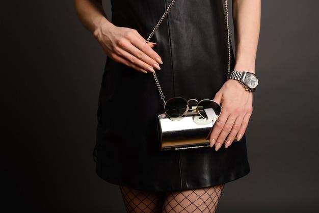 ファッションの女性は銀のクラッチを保持します