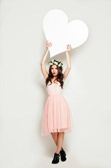 Женщина моды держа знамя большого белого сердца. фон продажи