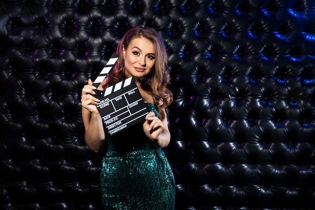 Fashion woman holding clapper board
