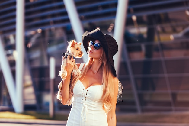 Fashion woman holding a sweet puppy